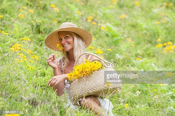 Austria, Altenmarkt-Zauchensee, Mid adult woman in alpine meadow with arnica