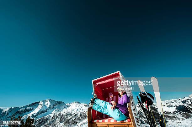 Austria, Altenmarkt-Zauchensee, skier sitting in hooded beach chair in the mountains enjoying glass of champagne