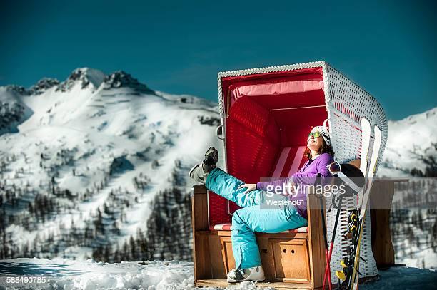 Austria, Altenmarkt-Zauchensee, skier sitting in hooded beach chair in the mountains