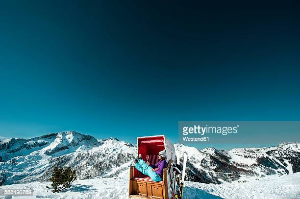 Austria, Altenmarkt-Zauchensee, skier sitting in hooded beach chair in the mountains