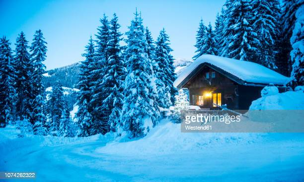 austria, altenmarkt-zauchensee, sledges, snowman and christmas tree at illuminated wooden house in snow at dusk - tranquil scene stock pictures, royalty-free photos & images