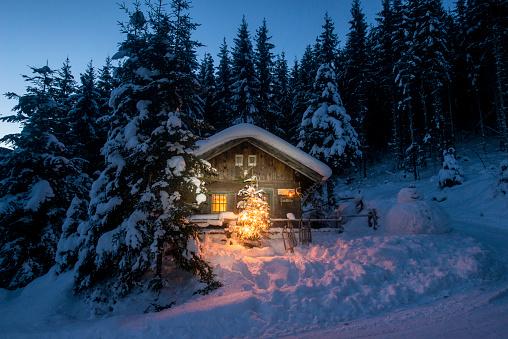 Austria, Altenmarkt-Zauchensee, sledges, snowman and Christmas tree at illuminated wooden house in snow at night - gettyimageskorea