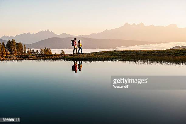 austria, altenmarkt-zauchensee, young couple at mountain lake in the lower tauern - autriche photos et images de collection