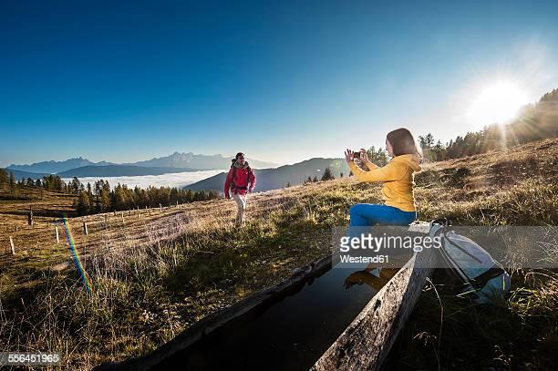 Austria, Altenmarkt-Zauchensee, young couple taking picture on hiking trip at Niedere Tauern