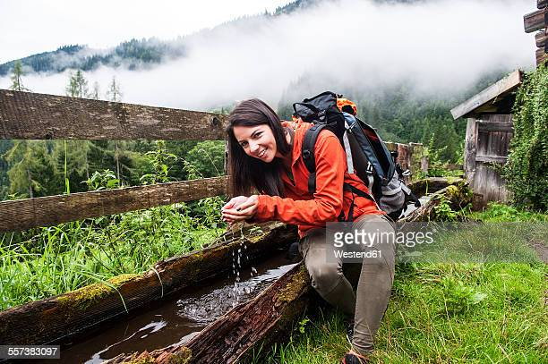 Austria, Altenmarkt-Zauchensee, young female hiker having a rest at a fountain