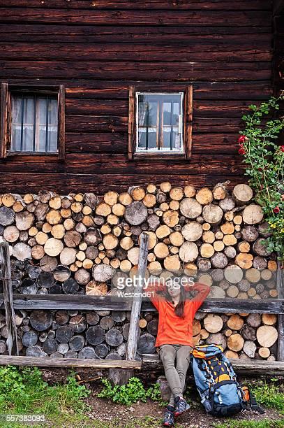 Austria, Altenmarkt-Zauchensee, young female hiker having a rest in front of Alpine cabin
