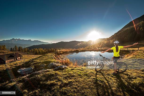 Austria, Altenmarkt-Zauchensee, young woman with mountain bike in the mountains at sunrise