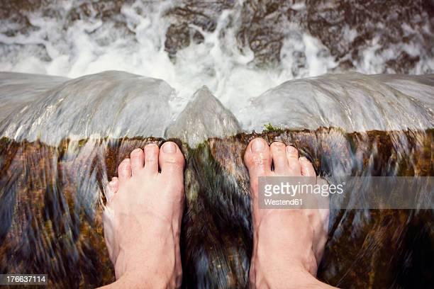 austria, barefooted man standing at edge of waterfall - am rand stock-fotos und bilder