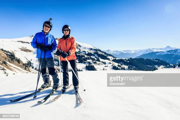 austria, damuels, couple with action cam skiing in winter landscape - blue film video stock-fotos und bilder