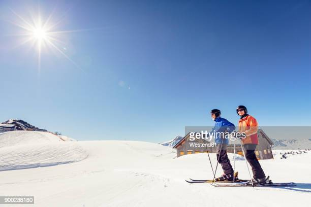austria, damuels, couple with skiers in winter landscape - ski holiday fotografías e imágenes de stock