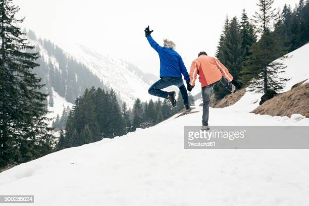 Austria, Damuels, happy senior couple jumping in winter landscape