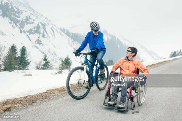 Austria, Damuels, senior couple with bike and wheelchair enjoying a winter day