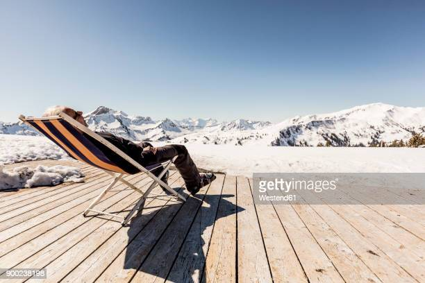 austria, damuels, senior man relaxing in deckchair on sun deck in winter landscape - ski holiday fotografías e imágenes de stock