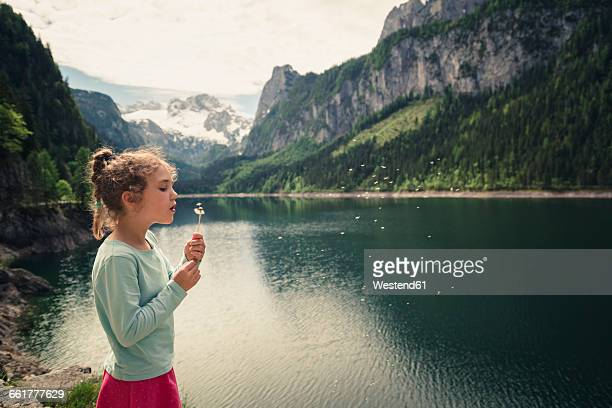 Austria, Gosau, girl with blowball at Gosausee