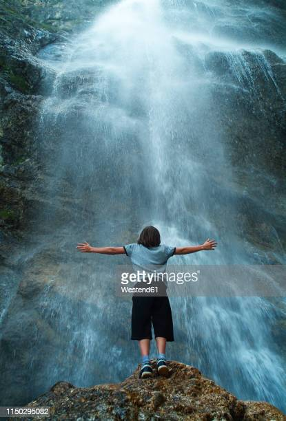 austria, hochkoenig, rear view of boy standing at waterfalll with outstretched arms - wasserfall stock-fotos und bilder