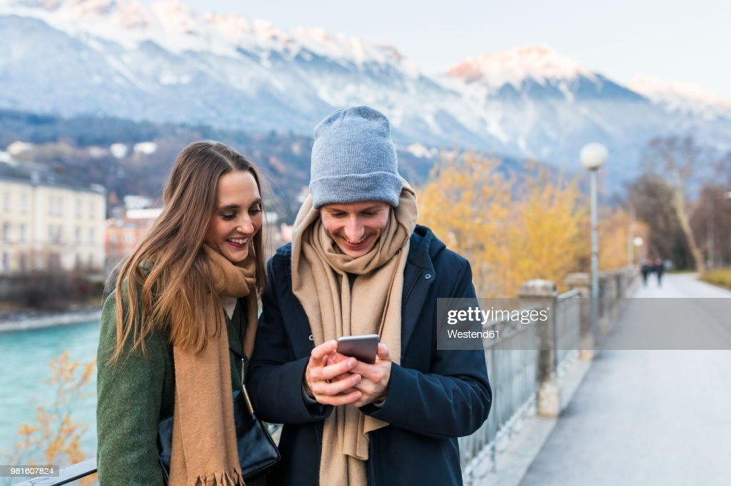 Austria, Innsbruck, happy young couple looking at cell phone : Stock Photo