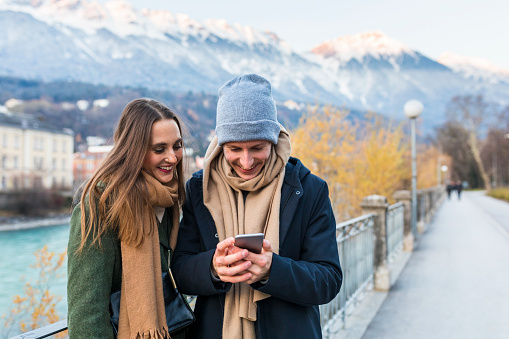 Austria, Innsbruck, happy young couple looking at cell phone - gettyimageskorea
