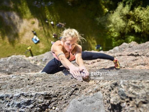 austria, innsbruck, hoettingen quarry, woman climbing in rock wall - klettern stock-fotos und bilder