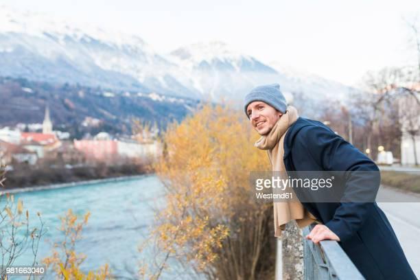 austria, innsbruck, portrait of smiling young man looking at distance - mütze stock-fotos und bilder