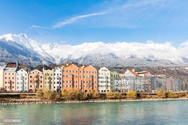 austria, innsbruck, row of houses in front of nordkette mountains with inn river in the foreground - インスブルック ストックフォトと画像