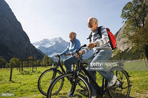 Austria, Karwendel, Couple cycling through meadow, mountains in background