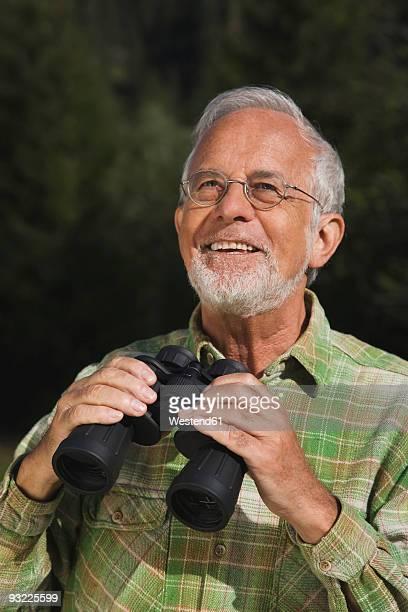 Austria, Karwendel, Senior man holding binoculars, looking up