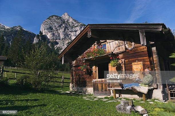 Austria, Karwendel, Senior man sitting in front of log cabin, reading a book