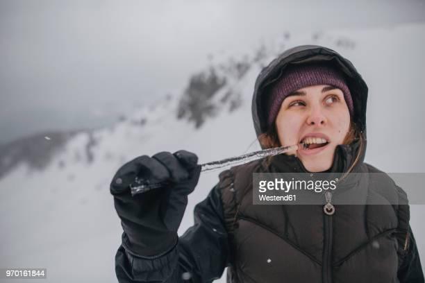 austria, kitzbuehel, portrait of young woman biting icicle - froid humour photos et images de collection