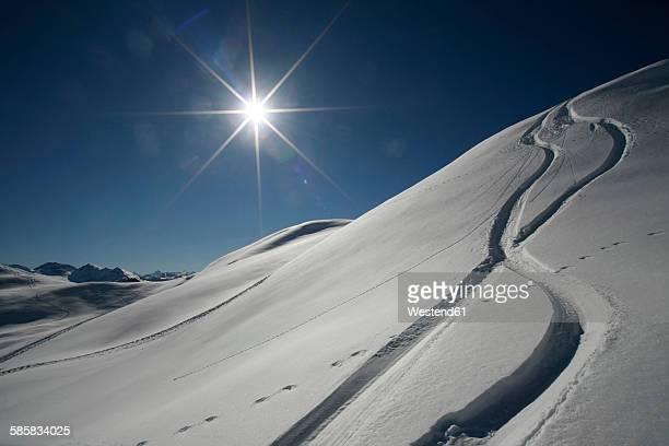austria, kitzbuehel, snow with ski tracks against the sun - schneebedeckt stock-fotos und bilder