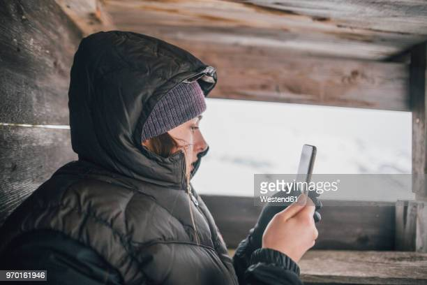 austria, kitzbuehel, young woman in raised hide looking at cell phone in winter - portable information device stock-fotos und bilder