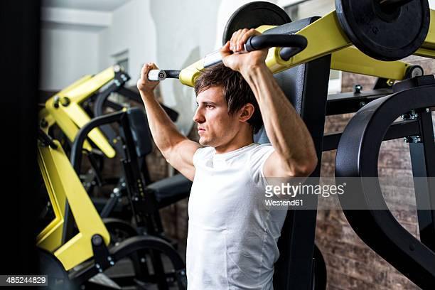 Austria, Klagenfurt, Man in fitness center doing machine workout