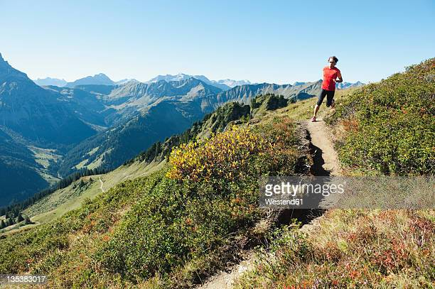 Austria, Kleinwalsertal, Mid adult man running on mountain trail