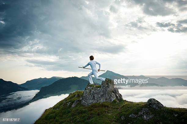 austria, kranzhorn, mid adult woman exercising stick fighting on mountain top - martial arts stock photos and pictures