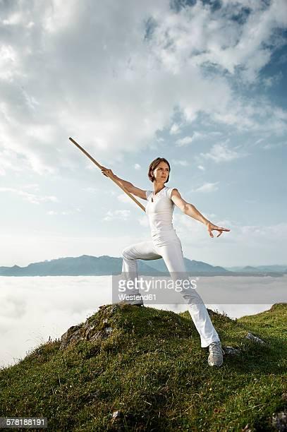 austria, kranzhorn, mid adult woman exercising stick fighting on mountain top - vechtkunst stockfoto's en -beelden