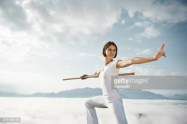 Austria, Kranzhorn, Mid adult woman exercising stick fighting on mountain top