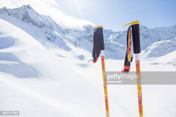 Austria, Kuehtai, ski sticks before mountainscape in winter