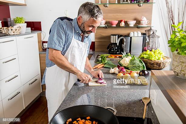 Austria, Man in kitchen chopping onions