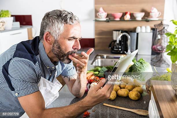 Austria, Man in kitchen holding digital tablet, looking for recipe