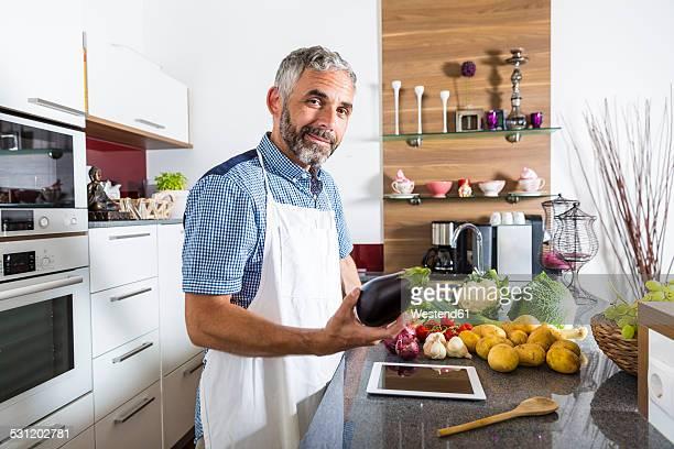 Austria, Man in kitchen with digital tablet preparing food