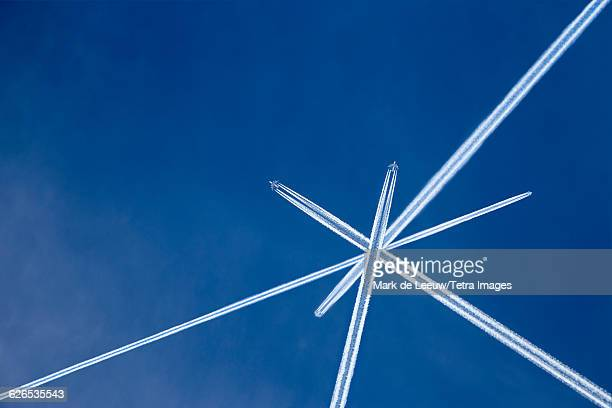 Austria, Maria Alm, Crossed vapor trails of airplanes in blue sky