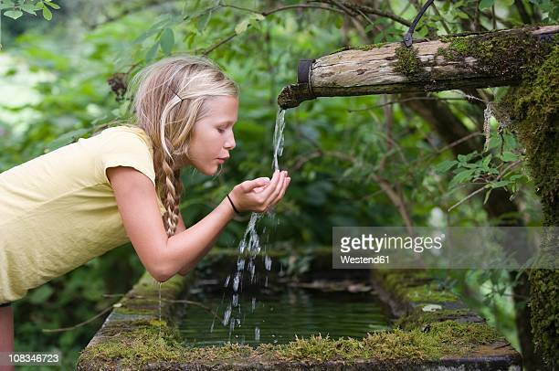 austria, mondsee, girl (12-13 years) drinking water from water spout - 12 13 years stock-fotos und bilder