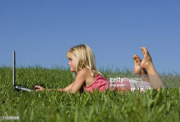austria, mondsee, girl (4-5) lying on meadow, using laptop - barefoot feet up lying down girl stock photos and pictures