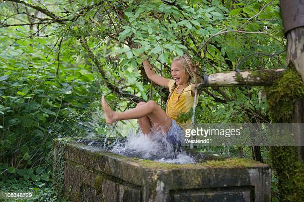 austria, mondsee, girl (12-13 years) playing with water in water trough - 12 13 years stock-fotos und bilder