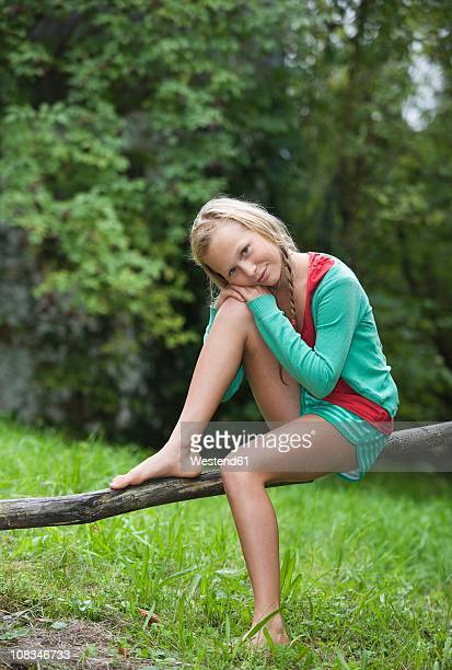 austria, mondsee, girl (12-13 years) sitting on branch, portrait - 12 13 years stock-fotos und bilder