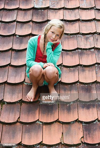 austria, mondsee, girl (12-13 years) sitting on roof top, portrait - 12 13 years stock-fotos und bilder