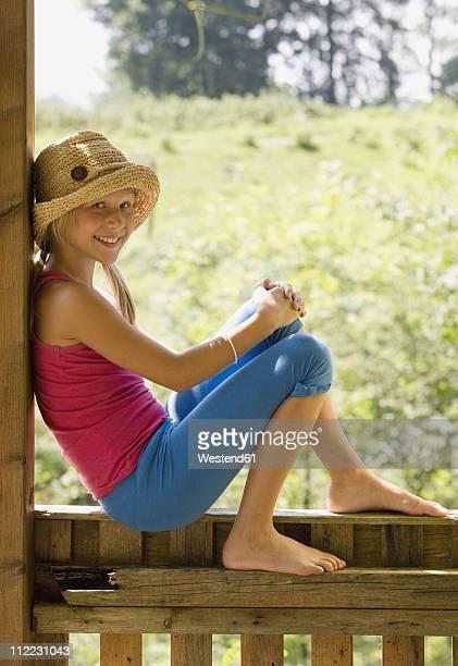 Austria, Mondsee, Girl (10-11) sitting on wooden railings, smiling, portrait