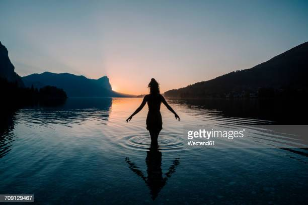 austria, mondsee, lake mondsee, silhouette of woman standing in water at sunset - dämmerung stock-fotos und bilder