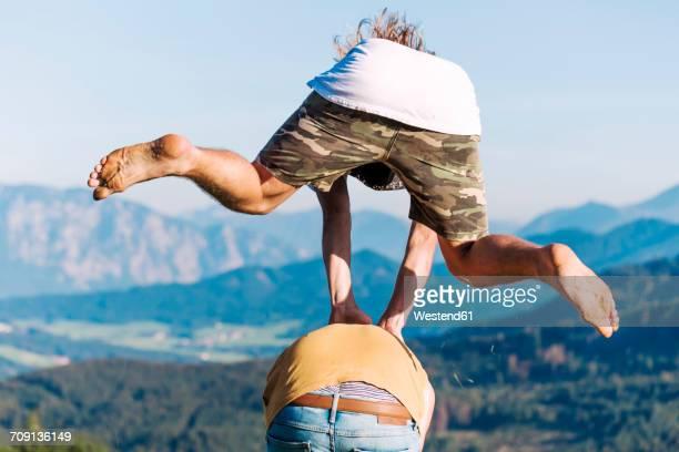 Austria, Mondsee, Mondseeberg, two young men leapfrogging