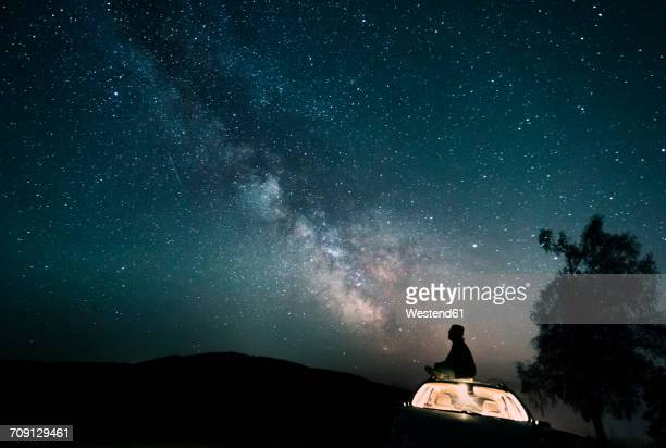 Austria, Mondsee, silhouette of man sitting on car roof under starry sky