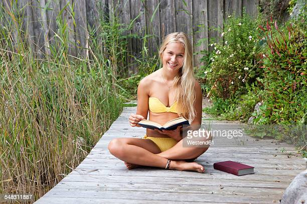 austria, mondsee, teenage girl reading on jetty - girls sunbathing stock pictures, royalty-free photos & images